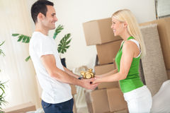 Saving for new home. Couple standing in new home  with piggybank Royalty Free Stock Image