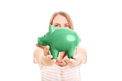 Saving is always an option. Young girl holding a piggy bank isolated on white background Stock Photo