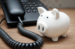Saving on phone bills - piggy bank and phone Royalty Free Stock Images