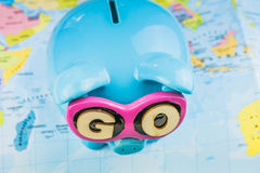Saving piggy bank from TOP view. GO slogan on sunglasses . Pig is staying on the world map ready for travel.  Royalty Free Stock Photography