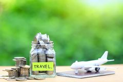 Saving planning for Travel budget of holiday concept,Financial,Stack of coins money in the glass bottle and airplane on passport. With natural green background royalty free stock photo