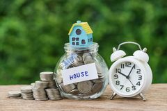 Saving property or long term mortgage concept as glass jar with. Full of coins and miniature house label as House with white alarm clock Stock Image