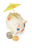 Saving for raining days. Cute piggy bank with colorful umbrella and US coins on white background Royalty Free Stock Image