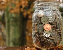 Saving for a rainy day jar with coins and rain. Stock Image