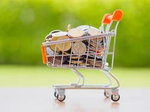 Saving for shopping concept,. Stack of coins and coins in cart Royalty Free Stock Image
