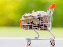 Saving for shopping concept. Saving for shopping concept, stack of coins and coins in cart Royalty Free Stock Image