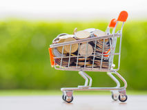 Saving for shopping concept,. Stack of coins and coins in cart Stock Photos