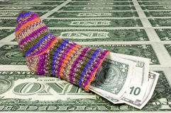 Saving sock. A saving sock on a sea of many one dollar bills. With space for copy stock photo