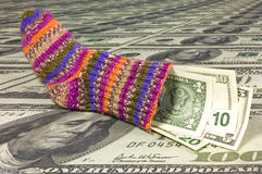 Saving sock. A saving sock on a sea of many one hundred dollar bills. With space for copy stock images