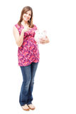 Saving some money during pregnancy. Full length view of a beautiful young Latin woman holding a piggy bank and saving some money during her pregnancy Stock Photo