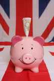 Saving ten pounds with piggybank Royalty Free Stock Photo