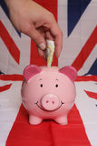 Saving ten pounds with piggybank Royalty Free Stock Images
