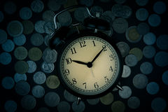 Saving time, Alarm clock with coins isolated on black background Stock Photography