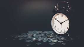 Saving time, Alarm clock with coins isolated on black background. with vintage filter. Stock Photo