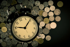 Saving time, Alarm clock with coins isolated on black background. with vintage filter. Stock Photos