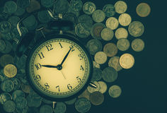 Saving time, Alarm clock with coins isolated on black background. with vintage filter. Stock Images