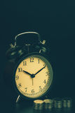 Saving time, Alarm clock standing with coins isolated on black background. with vintage filter. Stock Images
