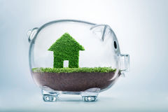 Saving to buy a house or home savings concept. With grass growing in shape of house inside transparent piggy bank Stock Photos