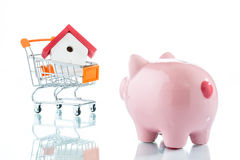 Saving to buy a house. Piggy bank, house and a shopping trolley Stock Photography