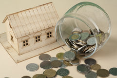 Saving to buy a house, real estate or home savings. Piggy bank, coins and toy model Stock Photos