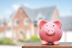 Saving to buy a house. Real estate or home savings, piggy bank in front of property Royalty Free Stock Images