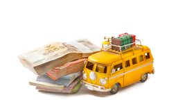 Saving for travel. Miniature  yellow bus with money background isolated on white background