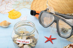 Saving for vacation. Money jar on a map concept for vacation costs and savings Stock Photo