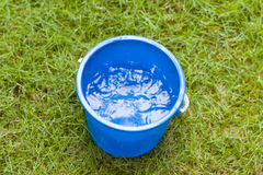Saving water. Collecting rain water in a blue pail Stock Image
