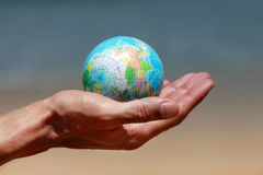 Saving world. Male hands with the small globe on a background of sand and sea Stock Image