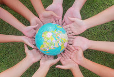 Saving the world. Hands touching earth globe with green grass background stock photography