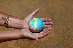 Saving world. Female hands with the small globe on a background of sand Royalty Free Stock Photos