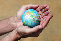 Saving world. Male hands with the small globe on a background of sand Royalty Free Stock Images