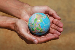 Saving world. Male hands with the small globe on a background of sand Stock Images