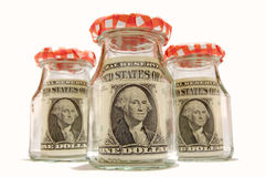 Savings. There are saved banknotes in three bottles. The background is white Royalty Free Stock Photos