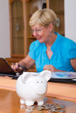 Savings. A senior woman working on computer on her finance and savings with piggy bank in front of her Royalty Free Stock Photography