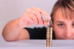 Savings. Young woman counting her savings Stock Image
