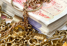 Savings. Gold jewelry on British Pounds royalty free stock photo