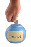Savings. Photograph of a human hand placing a coin in a blue moneybox, shot in studio and isolated on white Stock Photo