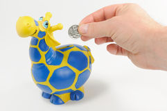 Savings. In giraffe moneybox for children on white background Royalty Free Stock Images