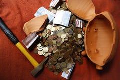Savings. A broken piggybank containing some savings Royalty Free Stock Image