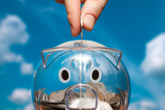 Savings. Saving, male hand putting a coin into piggy bank Royalty Free Stock Photo