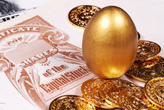 Savings. Gold Egg With Stock Certificate and Coins Stock Images