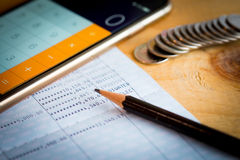 Savings account bank book. Pencil and smartphone used as calculator on wooden table Stock Photography