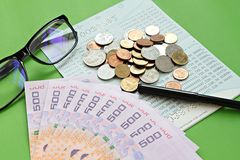 Savings account passbook, Thai money baht, coins, glasses and pen on green background Stock Photo