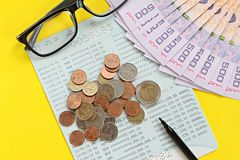 Savings account passbook, Thai money baht, coins, glasses and pen on yellow background Stock Photo