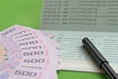 Savings account passbook, Thai money baht and pen on green background Stock Photo