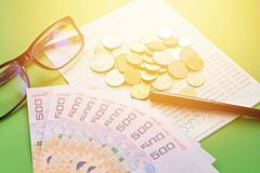Savings account passbook, Thai money , coins, eye glasses and pen on green background Stock Photos