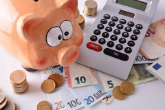 Savings and accounting with piggy bank money and calculator elev Stock Photos