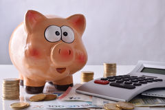 Savings and accounting with piggy bank money and calculator fron. Concept savings and accounting with piggy bank and stacked coins and bills, and calculator on Stock Images