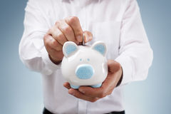 Savings. Businessman inserting a coin into a piggy bank concept for business savings, investment or banking Stock Photo